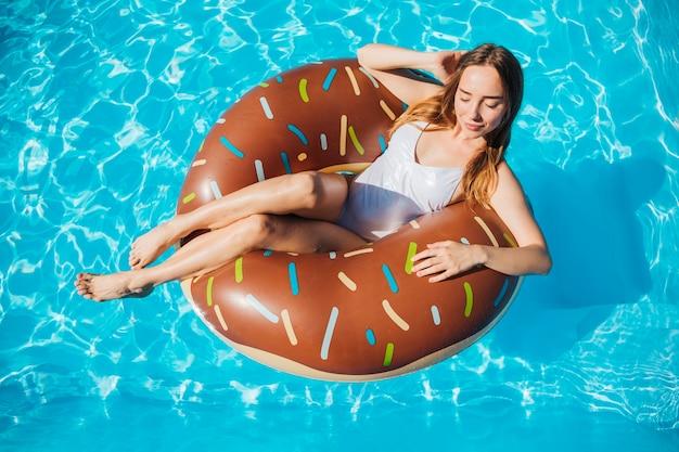 Hohe winkelfrau, die im donutschwimmenring aufwirft und lächelt