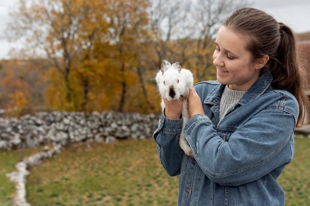 Hohe winkelfrau, die kaninchen hält