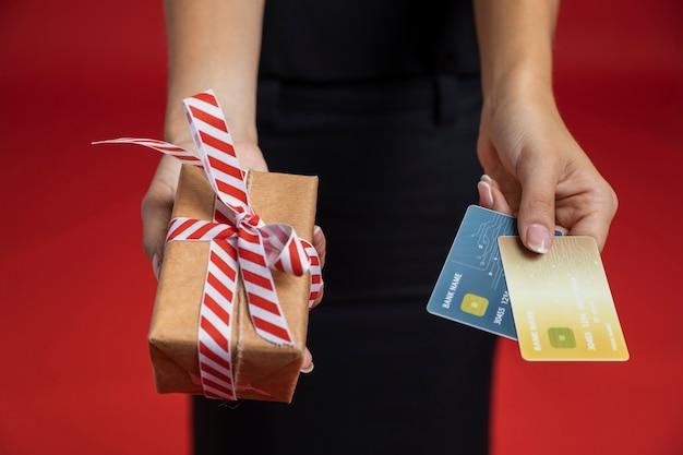 Hohe winkelfrau, die kreditkarten und geschenk hält
