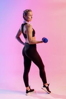 Hohe winkelfrau, die mit gewichten trainiert