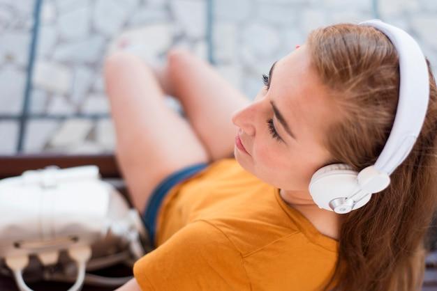 Hohe winkelfrau, die musik auf bank im bahnhof hört