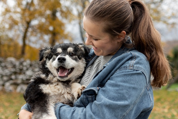 Hohe winkelfrau, die netten hund anhält