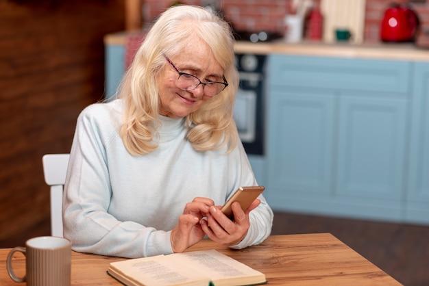 Hohe winkelfrau, die smartphone verwendet
