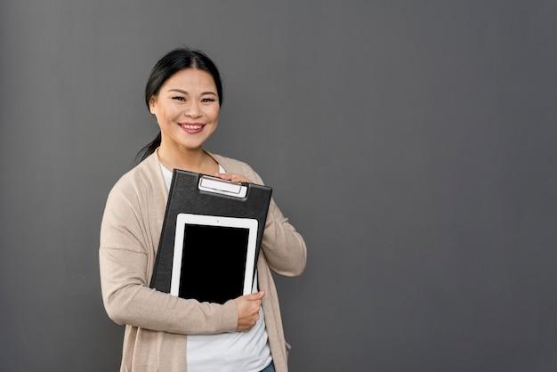 Hohe winkelfrau, die tablette und klemmbrett hält
