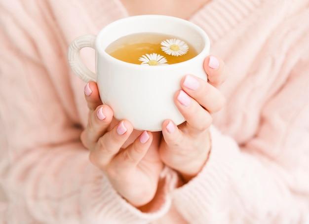 Hohe winkelfrau, die tasse mit tee und blumen hält