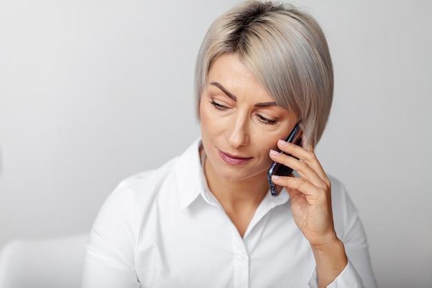 Hohe winkelfrau, die über telefon spricht