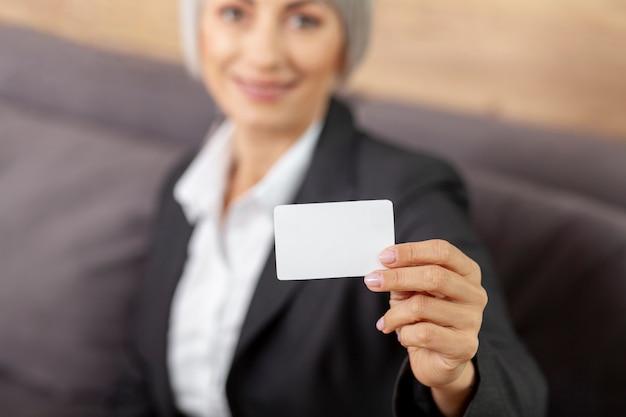 Hohe winkelfrau, die visitenkarte vorlegt