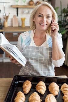 Hohe winkelfrau mit buch sprechend am telefon