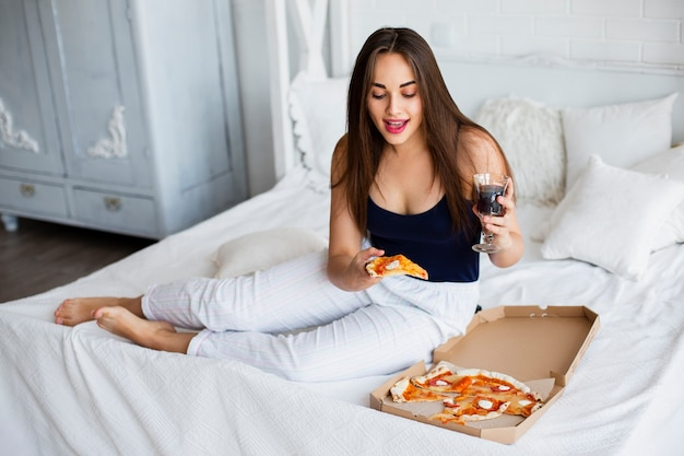 Hohe winkelfrau zu hause, die pizza isst