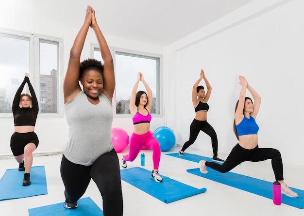 Hohe winkelfrauen, die auf matte trainieren