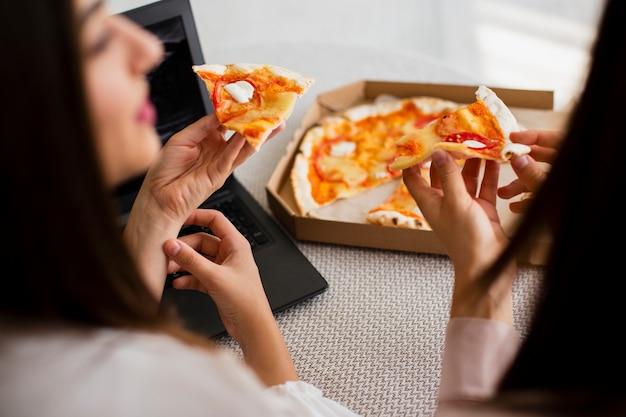 Hohe winkelfrauen, die köstliche pizza essen