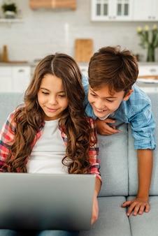 Hohe winkelgeschwister, die zusammen laptop verwenden