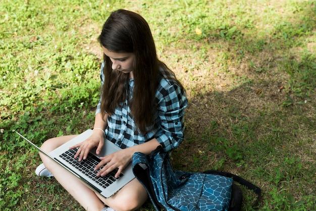 Hohe winkeljugendliche, die an laptop arbeitet