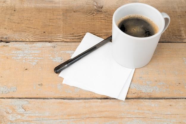 Hohe winkelkaffeetasse auf hölzernem hintergrund