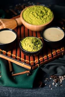 Hohe winkelschüsseln mit pulver des grünen tees und teegetränk