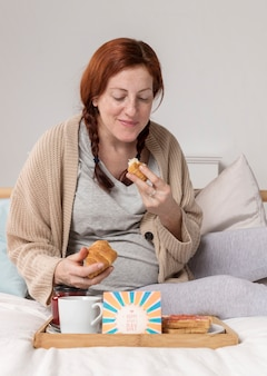Hohe winkelschwangere, die croissant genießt