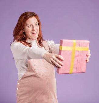 Hohe winkelschwangere, die geschenk betrachtet
