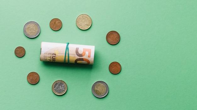 Hohe winkelsicht der aufgerollten eurobanknote mit münzen auf grünem hintergrund