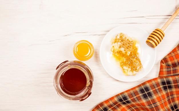 Hohe winkelsicht der bienenwabe und des honigglases