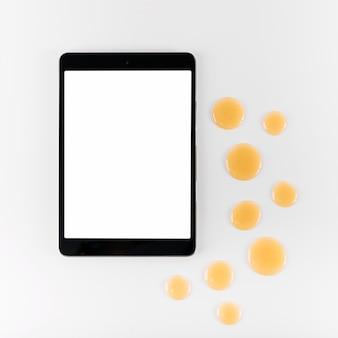 Hohe winkelsicht der digitalen tablette und tropfen des honigs auf weißem hintergrund