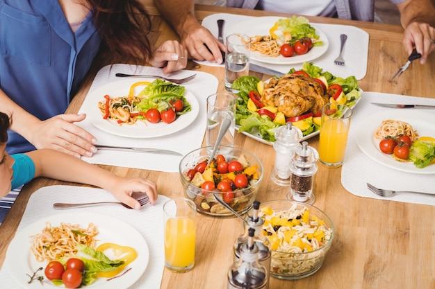 Hohe winkelsicht der familie mit lebensmittel auf speisetische
