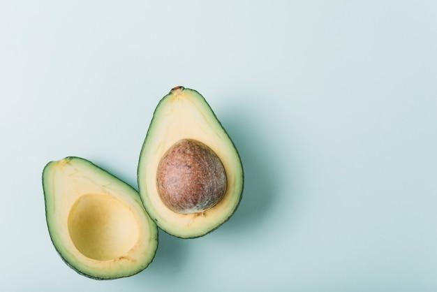 Hohe winkelsicht der frischen halbierten avocado auf grüner oberfläche