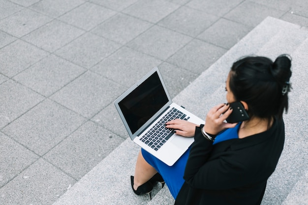 Hohe winkelsicht der geschäftsfrau, die laptop verwendet und am handy spricht