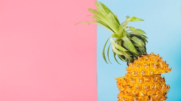 Hohe winkelsicht der geschnittenen ananas auf hintergrund des rosas und des blauen papiers