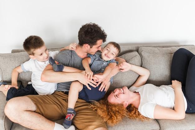 Hohe winkelsicht der glücklichen familie, die spaß auf sofa hat