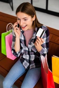 Hohe winkelsicht der glücklichen frau karte halten