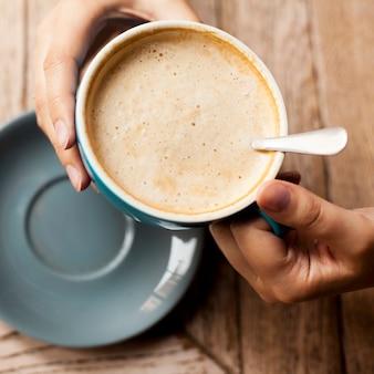 Hohe winkelsicht der hand der frau kaffeetasse mit schaumigem schaum halten