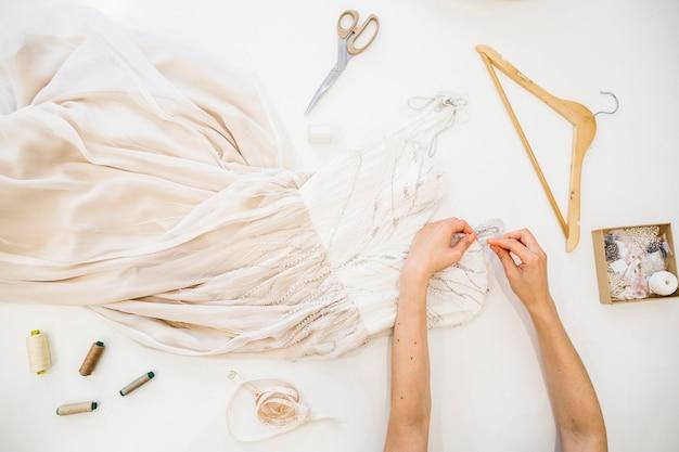 Hohe winkelsicht der hand eines modedesigners, die an kleid über weißem hintergrund arbeitet