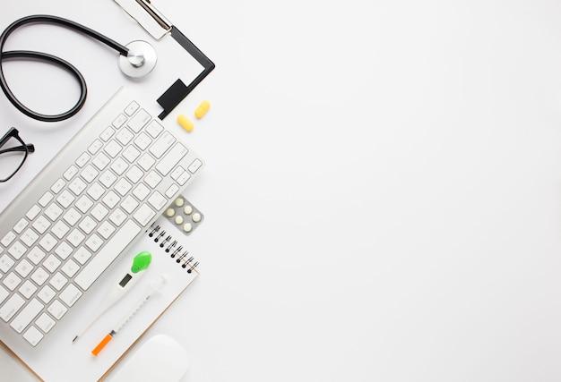 Hohe winkelsicht der medizinischen ausrüstung und der drahtlosen tastatur über hintergrund