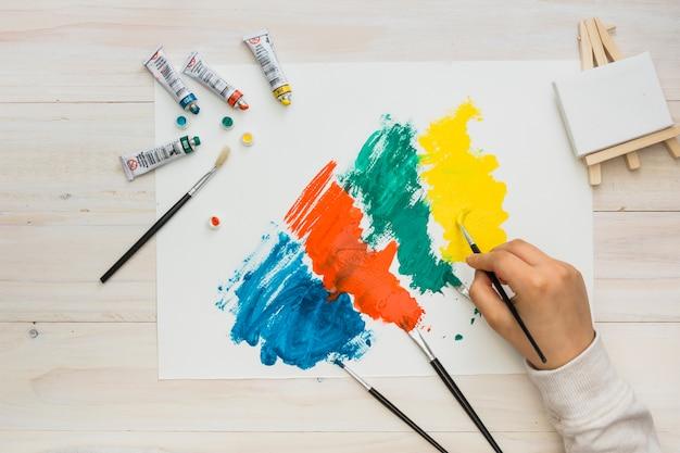 Hohe winkelsicht der menschlichen handmalerei auf weißbuch mit buntem pinselstrich