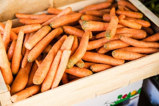 Hohe winkelsicht der orange karottenkiste am gemüsemarkt