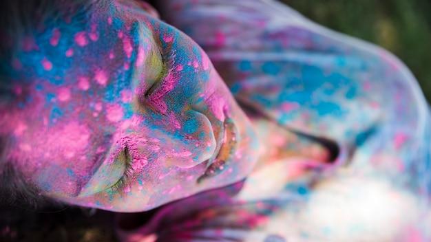 Hohe winkelsicht der rosa und blauen holi farbe auf dem gesicht der frau