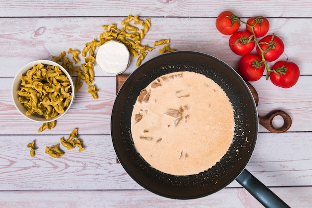 Hohe winkelsicht der zubereitung der italienischen geschmackvollen teigwaren auf hölzernem schreibtisch