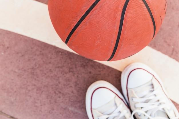 Hohe winkelsicht des basketballs und der turnschuhe