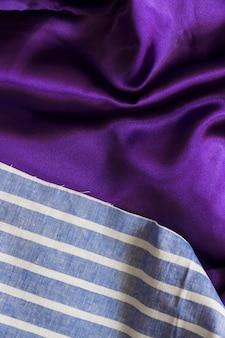 Hohe winkelsicht des blauen plaidgewebes und des glatten purpurroten stoffes