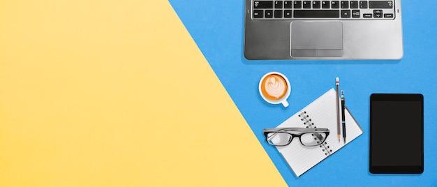 Hohe winkelsicht des bunten schreibtischs des büros mit kopienraum, laptop, notizbuch, tablette