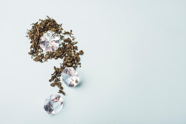 Hohe winkelsicht des diamanten und der trockenen blumenblumenblätter auf weißer oberfläche