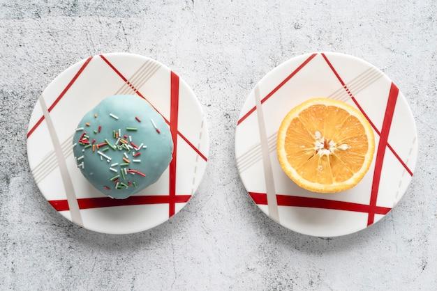 Hohe winkelsicht des donuts und der halbierten orange auf platte über konkretem hintergrund