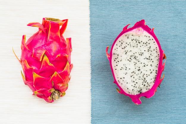 Hohe winkelsicht des drachen trägt auf bunte tischdecke früchte