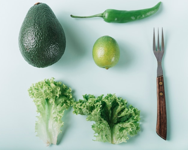 Hohe winkelsicht des frischen grünen gemüses mit gabel auf grüner oberfläche
