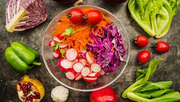 Hohe winkelsicht des frischen salats in der glasschüssel umgeben mit gemüse und früchten