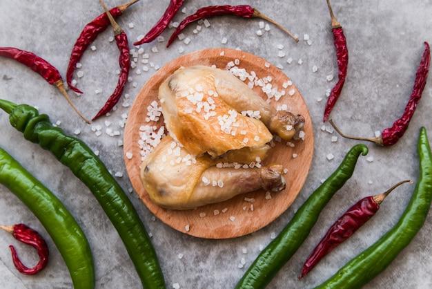 Hohe winkelsicht des gebackenen huhns schmücken mit salz und paprikas über konkretem hintergrund