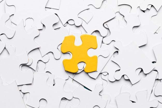 Hohe winkelsicht des gelben puzzlespielstückes über weißen puzzlespielstücken