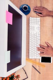 Hohe winkelsicht des geschäftsmannes arbeitend an computer am schreibtisch im büro