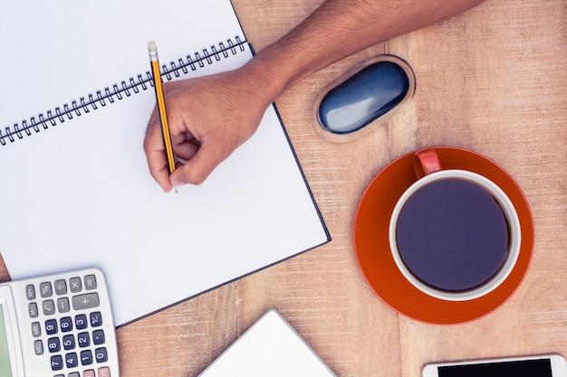 Hohe winkelsicht des geschäftsmannschreibens auf notizbuch durch kaffee am schreibtisch im büro