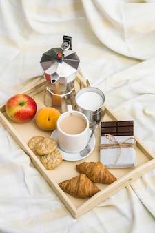 Hohe winkelsicht des gesunden frühstücks auf unordentlichem bedsheet